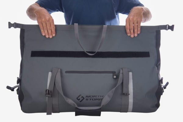 Showing the first step on how to roll the top closed of the 60 litre north storm roll top waterproof duffel bag. Shows two hands pinching the top of the bag together to create a seal