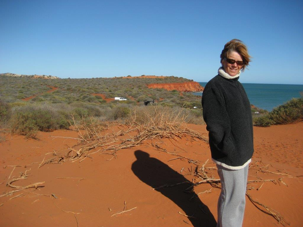 Photo of a lady standing on coastal cliffs with the red dirt of outback Australia all around her feet. The blue ocean is also in the background and in the distance.