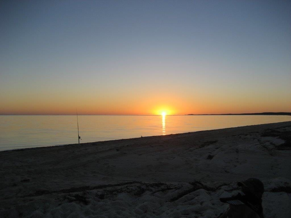 Photo of a beautiful sunset at Shark Bay in Western Australia with a fishing rod sticking out of the sand.