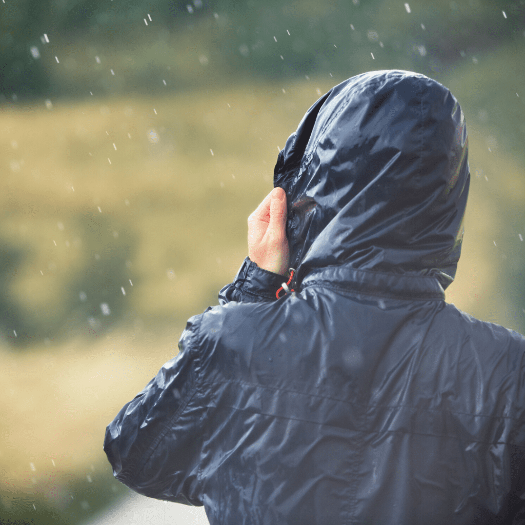 Person wearing a blue raincoat standing in the rain with their back to the camera