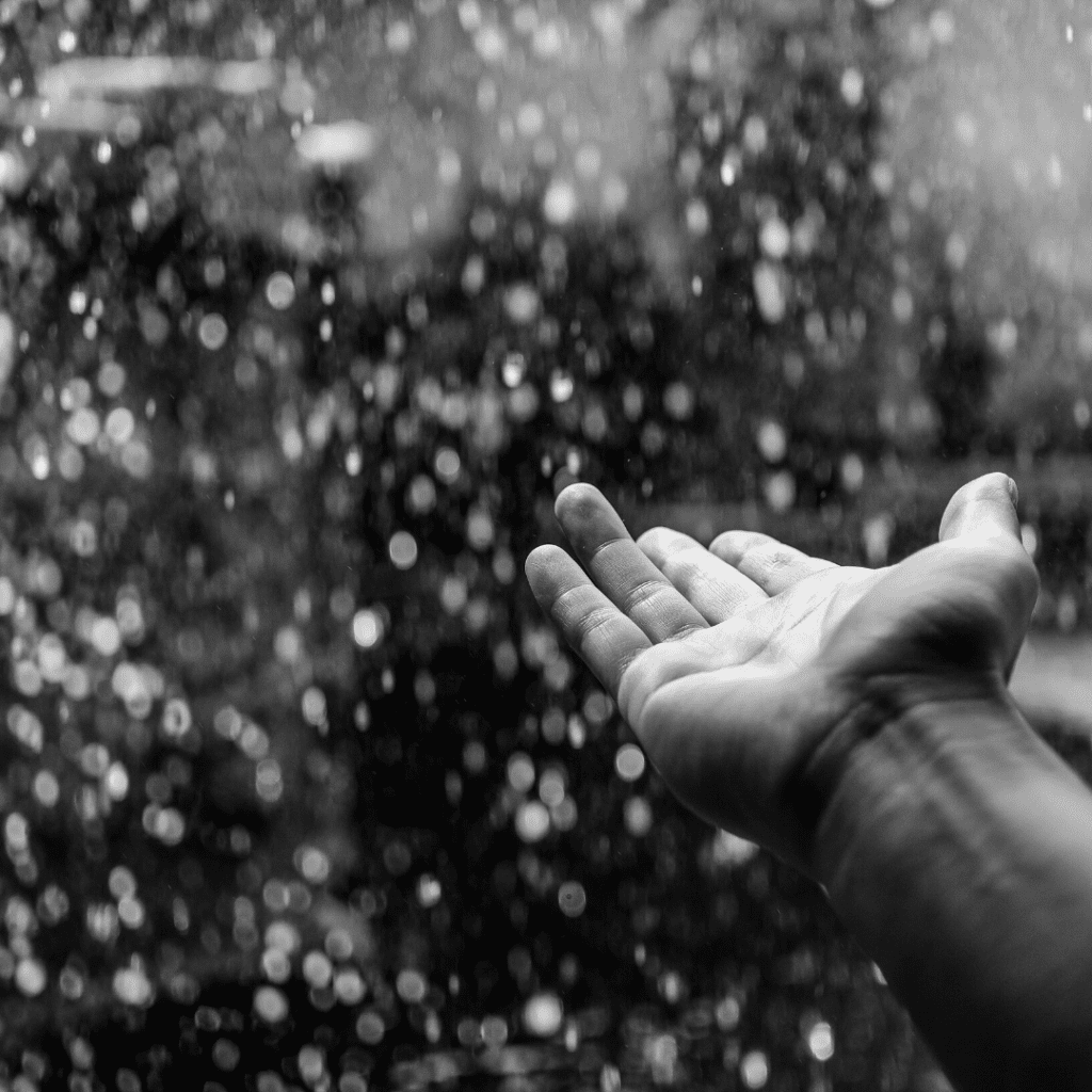 Black and White photo of a hand outstretched touching the rain that is falling