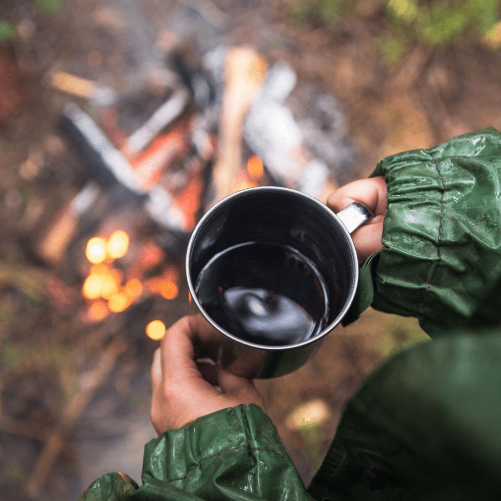 Photo of a person wearing a green waterproof jacket standing in front of a campfire drinking coffee in the rain.