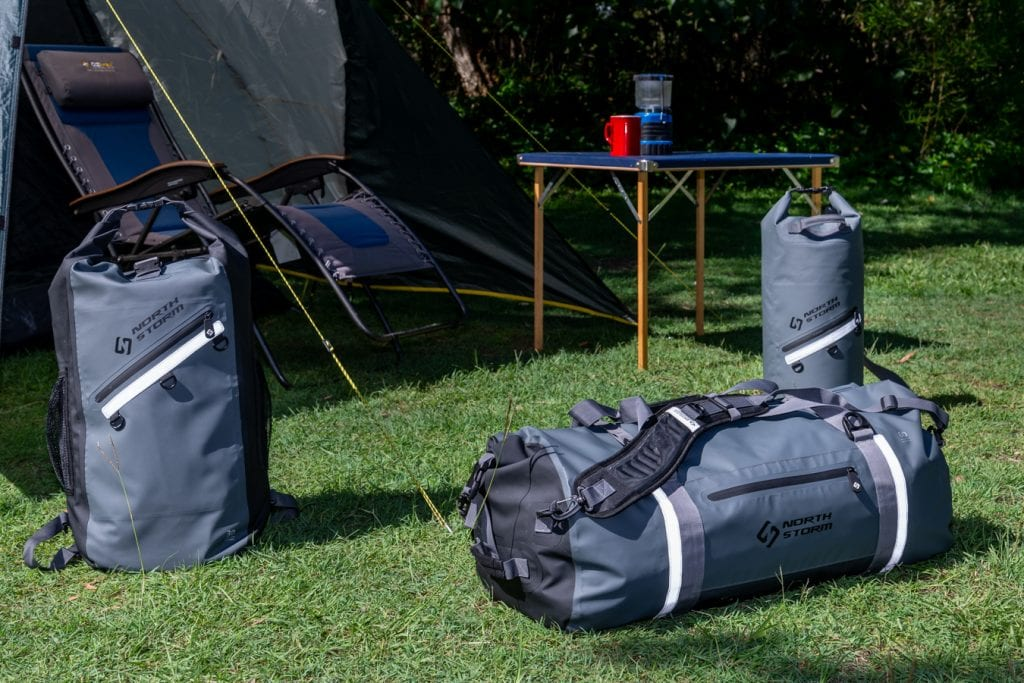 North Storm Bags at a campsite sitting in front of a tent in the grass. There is also a table set up with cup sitting on top of it.