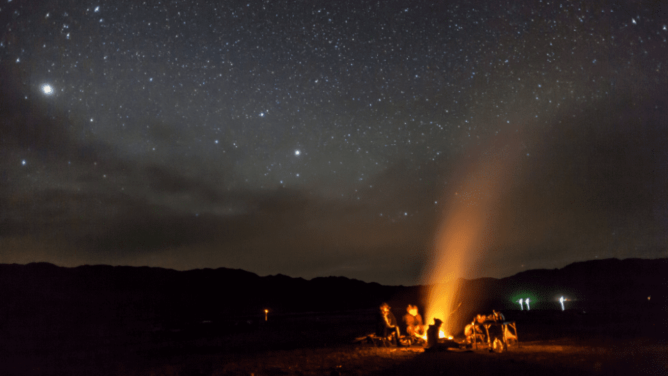 Group of people sitting around a campfire at night time. The sky is very clear and full of stars. The group of people are sitting in a circle and have the warm glow of the fire on their bodies.