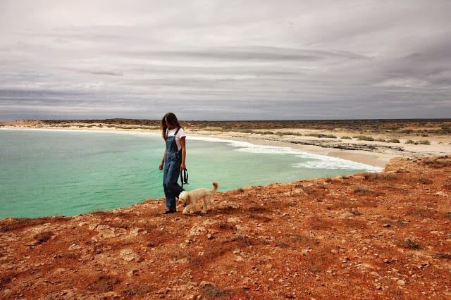 Salty travellers photo of a lady at WA's ningaloo reef walking along the cliff faces with the reef down in the background.