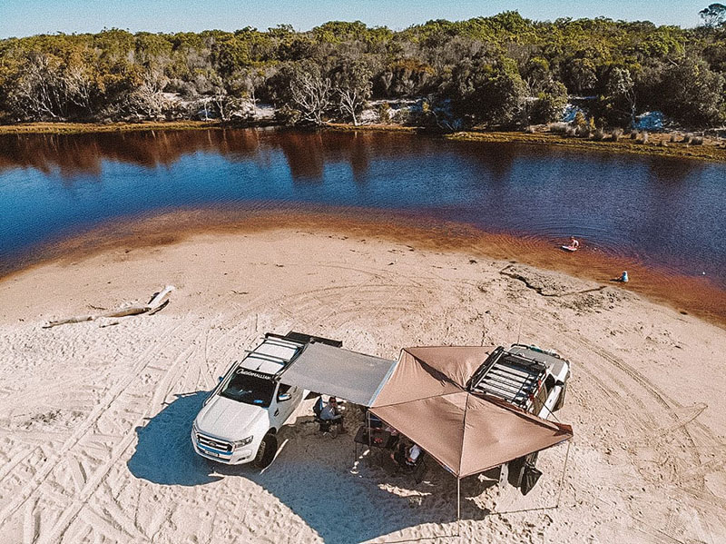 Big Oz Explorers have set up camp while they travel Australia. This photo shows them camped by the side of lagoon at Bribie Island. They have their four wheel drive set up with a bat winged canopy over head. The lagoon water is very brown and appears to be fresh water. There are trees lining the edge of water.