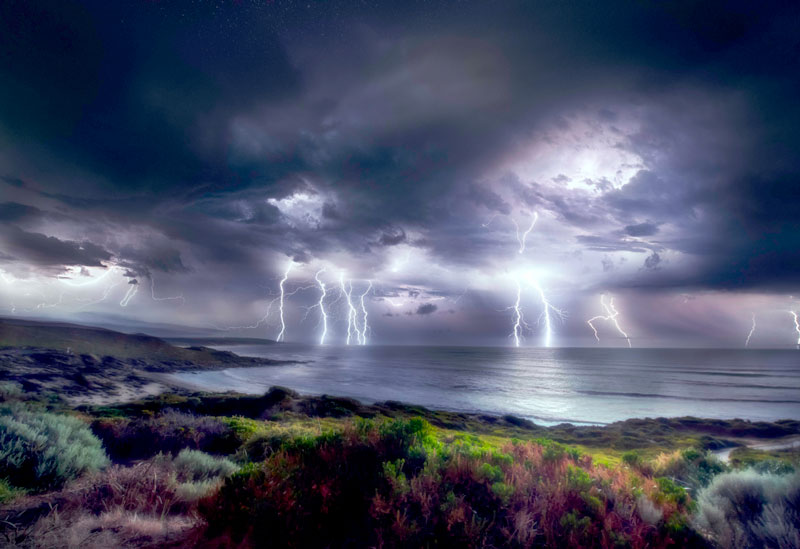 Photo of a magnificent storm with lightning and very grey clouds reflecting over the water