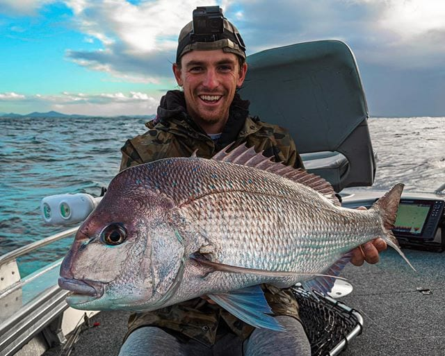 Photo of a young man holding a huge snapper he caught. He is wearing a head torch and smiling happily. The sea is in the background as he is on a boat. He is Tim Stenlake aka Timmy Turtle he is a North Storm waterproof bag ambassador