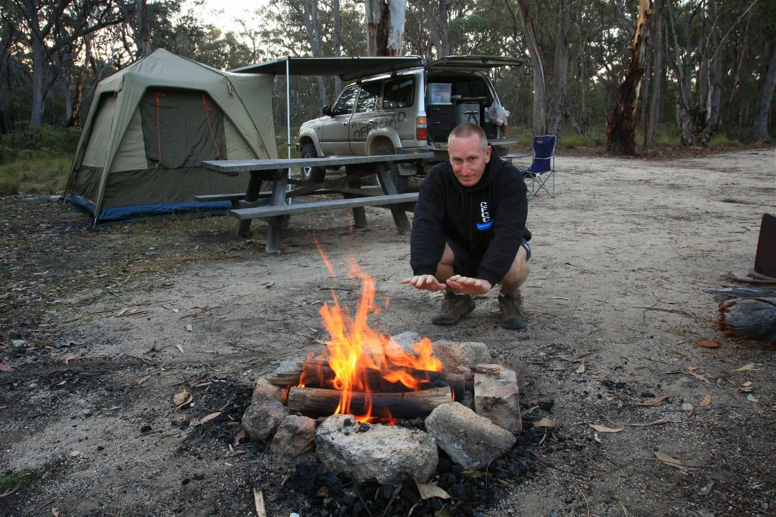 Kev smith from woolgoolgaoffroad squatting down and warming his hands by the campsite fire. His camping tent and four wheel drive in the background and surrounded by australian bush. Photo is part of the Kev Smith from woolgoolgaoffroad ambassador profile for North Storm waterproof bags.
