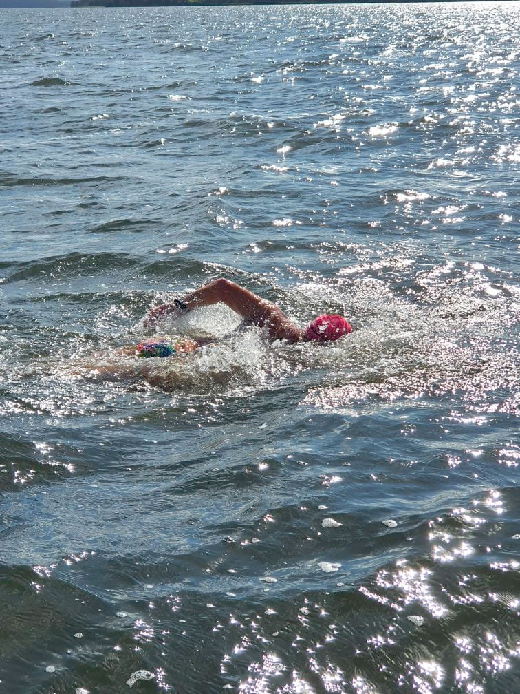 Man swimming in the ocean doing freestyle. He is wearing a swim cap.