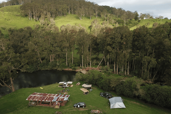 a birdseye view of the campsite at bossberries with trees, hills, tents and cars