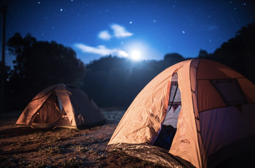 Photo of a 4 Wheel drive parked next to a tent under a very starry starry night sky