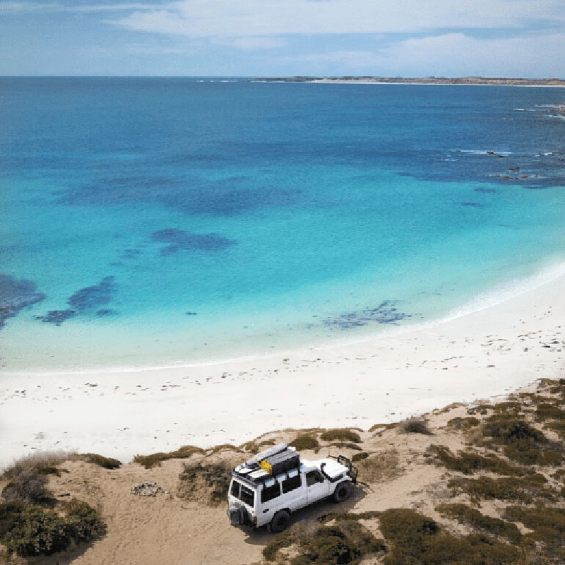Ariel view of the coast line with very blue beach or ocean waters, very clean white sand and a four wheel drive parked up on an embankment next to the beach. Corny Point, Yorke Peninsula SA - Along the coast offers a range of surf and awesome fishing!