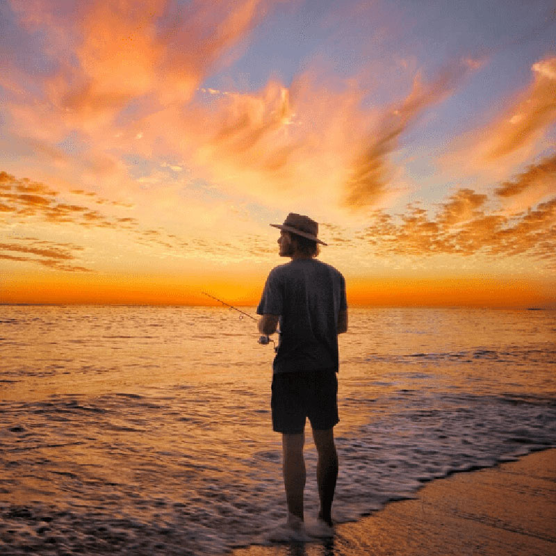 A man standing on the beach fishing with a beautiful orange and blue sunset happening over the sea. Coronation Beach Campground, WA - If you've got a 4WD you can adventure down the sandy track to find good waves and calm lagoons for diving. - Photo by the Salty Travellers.