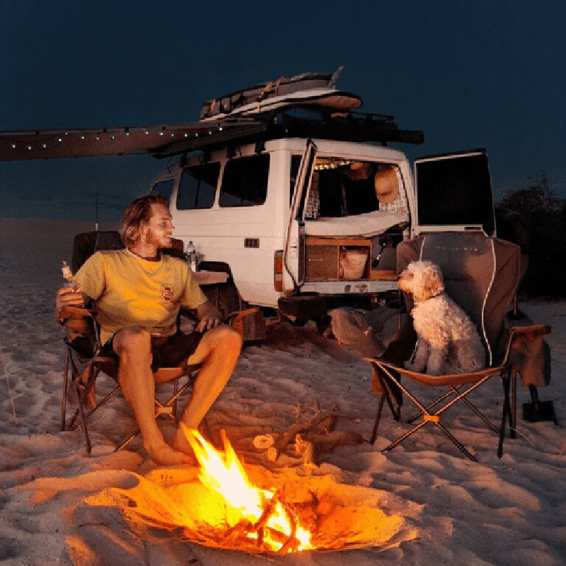 Photo of a man and his dog sitting on a chair each at a campsite. 4 wheel drive in the background and a campfire in front of them. They look very happy campers and relaxed. Lucky Bay, Coral Coast WA - You can drive along the beach and find a spot right in front of the huge lagoon where you can fish or even snorkel.