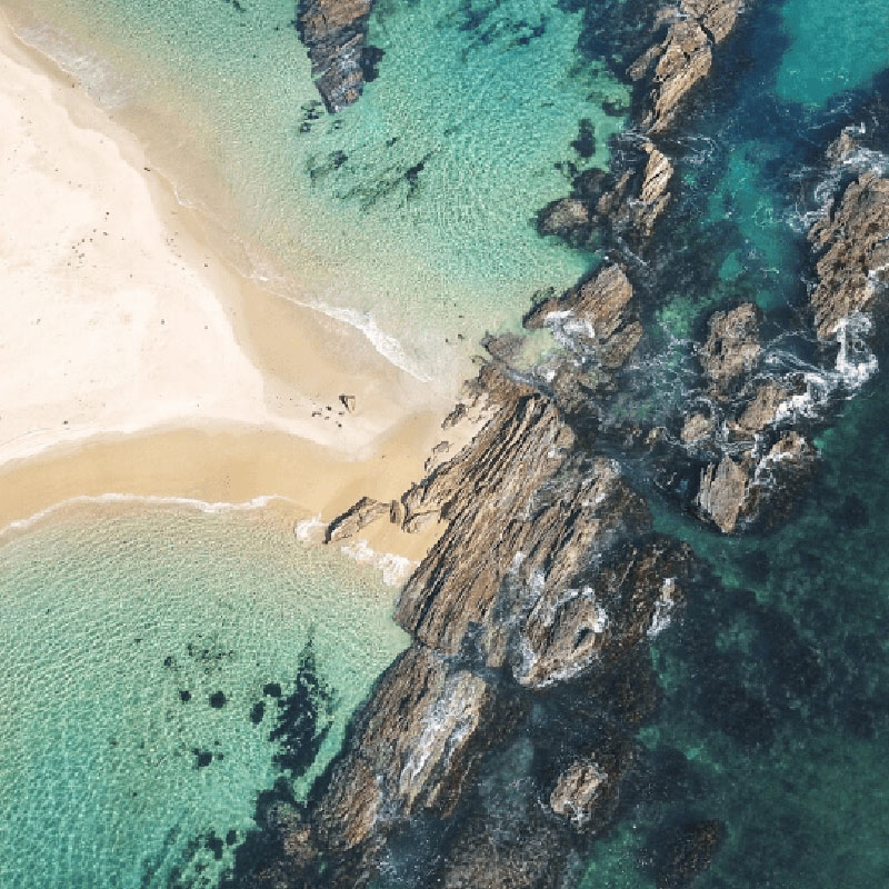Mystery Bay, NSW - Only 12km south of Narooma, this little piece of paradise offers spacious and shady campsites on the northern end of the bay.. This is an birds eye view of the bay with crystal clear water and rocky cliff faces protruding.