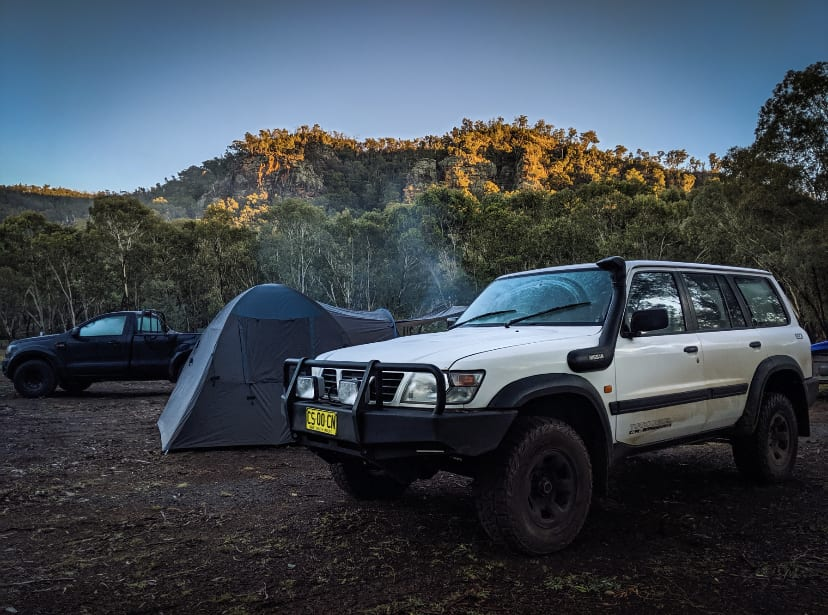 4 Wheel drive parked next to a tent with the sun rising in the background behind the mountains