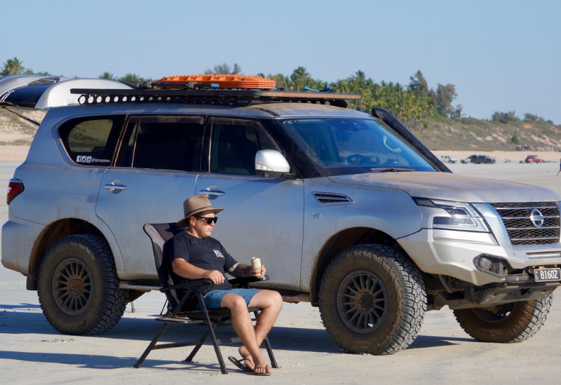 Big Oz Explorers Chris on the beach with a Great Northern Beer and 4x4